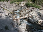 A small log bridge crosses the Inter Fork of the White River on Emmons Glacier View Trail.