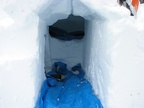 Here is the entrance to my completed igloo. The entrance has one blue tarp and the raised sleeping area has another. I made a cubby hole on the left in the entrance to store gear.